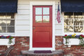 Red front door of an american home a also seen is white siding flag blue awning flowers and brick steps Stock Photography