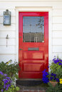 Red front door of an upscale home vertical shot a on a with a mail slot plants doorbell brick flooring and reflection in the Royalty Free Stock Photo
