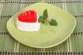 Red gelled cake with mint on green plate on a tablecloth made of bamboo Royalty Free Stock Image