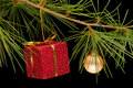 Red gift box and bauble on pine branch Royalty Free Stock Photos