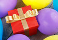 Red gift box with gold ribbon in balloons