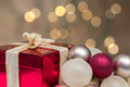 Red gift box with ribbon, baubles. Blurred  background with shining lights. Royalty Free Stock Photo
