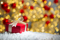 Red gift box on snow with abstact bokeh background. Royalty Free Stock Photo