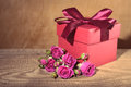 Red gift box tied with decorative ribbon and bouquet rose flower