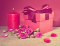 Red gift box tied with decorative ribbon, bouquet rose flowers,