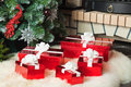 Red gift boxes near christmas tree and fireplace a Stock Photography