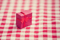 Red gift on tablecloth photo with filter Royalty Free Stock Image