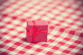Red gift on tablecloth photo with filter Royalty Free Stock Photo