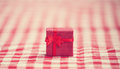 Red gift on tablecloth photo with filter Royalty Free Stock Images