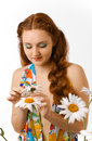 Red girl telling fortunes by camomile youth woman is looking at a chamomile and plucking its petals she is guessing flower there Royalty Free Stock Photography