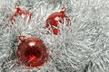 Red glass baubles on silver tinsel. Stock Photos