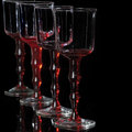 Red glass goblets four for wine on black Royalty Free Stock Photos