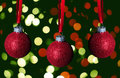 Red glitter christmas ornaments on green background Stock Image