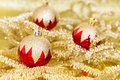 Red and gold christmas baubles on background of defocused golden lights Royalty Free Stock Photo