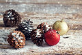 Red and gold christmas ornament pine cones on wooden