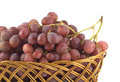 Red grape on branch in straw wicker basket isolated brown white Stock Photo