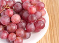 Red grape branch in white plate on straw tray clo Royalty Free Stock Photos