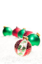 Red, green and colorful Christmas  baubles on snow Royalty Free Stock Image