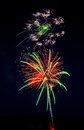Red and green fireworks lighting area at bottom Stock Photography