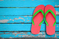 Red and green flip flop on blue wood Royalty Free Stock Photos