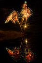 Red green and gold fireworks reflected in a murky lake Stock Photography
