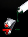 Red and green paints follow from the tubes Stock Image