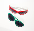 Red and green sunglasses a pair of plastic framed on a white background Royalty Free Stock Photo