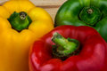 Red Green and Yellow Capsicums on a Wooden Table Royalty Free Stock Photo