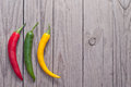 Red green and yellow hot chili pepper on wooden planks Royalty Free Stock Photography