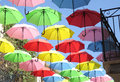 Red, green, yellow, pink, umbrellas flying over city street Royalty Free Stock Photo