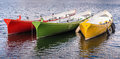 Red green yellow rowing boats three of different colours moored on a lake Royalty Free Stock Photo