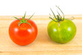 Red and green zebra tomatoes two one one on a chopping board Stock Photos