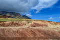 Red ground cross section in foreground partly cloudy sky and high mountains in the distance Royalty Free Stock Photo