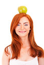 Red hair woman with green apple on her head over white background Stock Photography
