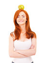 Red hair woman with green apple on her head over white background Stock Images