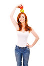 Red hair woman with green apple on her head over white background Stock Image