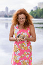 Red hair woman looking on couple of snails in her hand summer kyiv obolon embankment Stock Photo