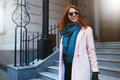 Red haired beautiful girl is walking by the street in a pink coat and blue scarf, with sunglasses. Royalty Free Stock Photo
