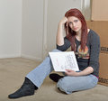 Red haired caucasian woman with evicition notice cute young sitting on floor of home holding a generic eviction letter in front of Royalty Free Stock Photos