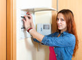 Red haired cute woman turning off the light switch at power cont control panel in home Royalty Free Stock Photos