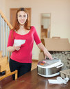 Red haired female unpacking and reading user manual for new croc cheerful woman crock pot Royalty Free Stock Photography