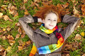 The red-haired girl in autumn leaves. Royalty Free Stock Photos