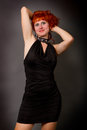 Red haired girl in a black dress beautiful young on gray background Stock Photos