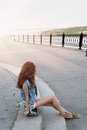 Red haired girl sitting near her scateboard vertical image Royalty Free Stock Photo