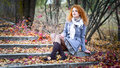 Red haired girl thoughtful outdoors sitting on stairs covered fallen leaves Stock Image