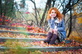 Red haired girl thoughtful outdoors sitting on stairs covered fallen leaves Royalty Free Stock Images