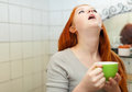 Red haired teenager gargling throat in bathroom her at home Royalty Free Stock Images