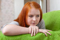 Red haired unhappy teenager on sofa at home Stock Image