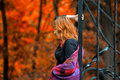 Red haired woman in the autumn park a cast iron gates Stock Image