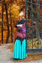 Red haired woman in the autumn park a cast iron gates Stock Photo